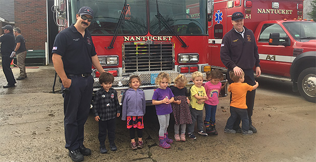 Nantucket firefighters Nate Barber and Sean Mitchell with preschool children in front of a fire truck. Photo credit: Sean Mitchell/Special to E&E News